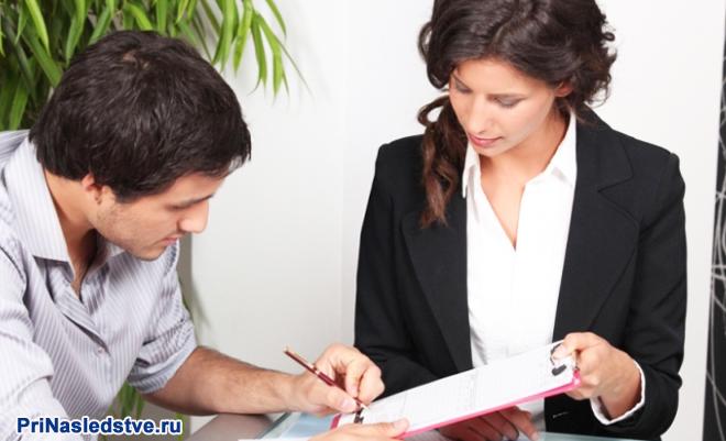 Мужчина подписывает документ, рядом сидит работница банка