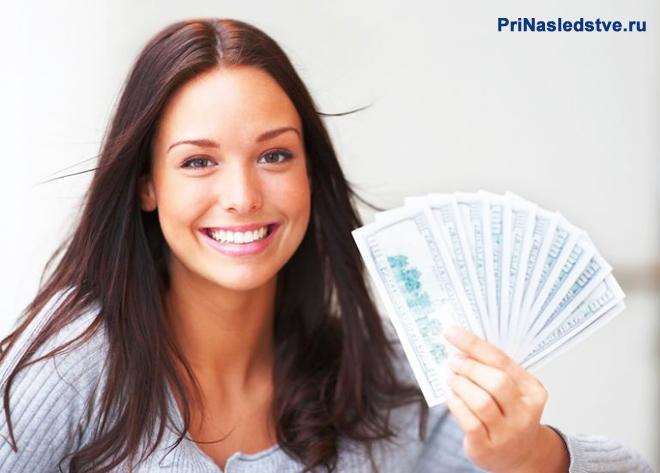 Девушка держит в руке веер из денежных купюр