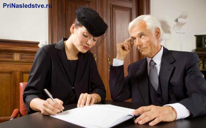 Девушка в черном сидит за столом и подписывает бумаги рядом с мужчиной