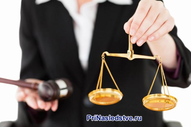 Юрист держит в руке весы Фемиды