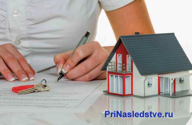 Девушка в белой рубашке ставит подпись на документе, рядом стоит домик
