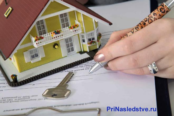 Девушка заполняет документы, рядом стоит желтый домик с красной крышей