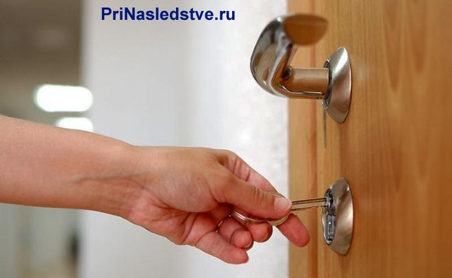 Человек открывает дверь ключом