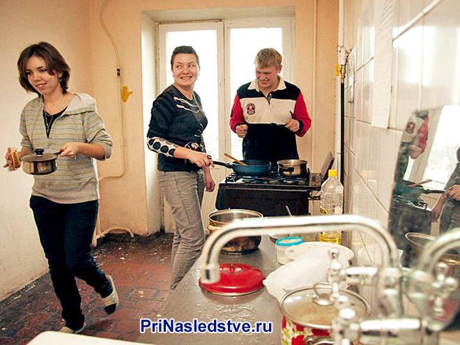Люди готовят еду на общей кухне