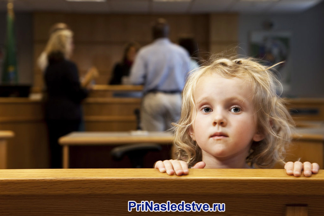 Маленькая девочка, на заднем фоне взрослые