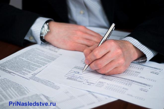 Бизнесмен заполняет бланки документов