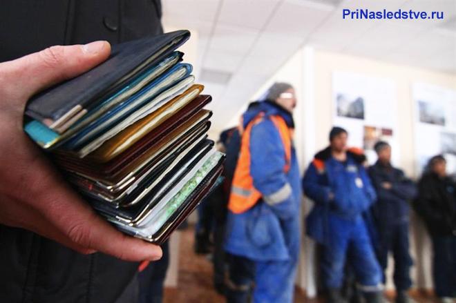 Мужчина держит в руке паспорта на фоне работников в форме