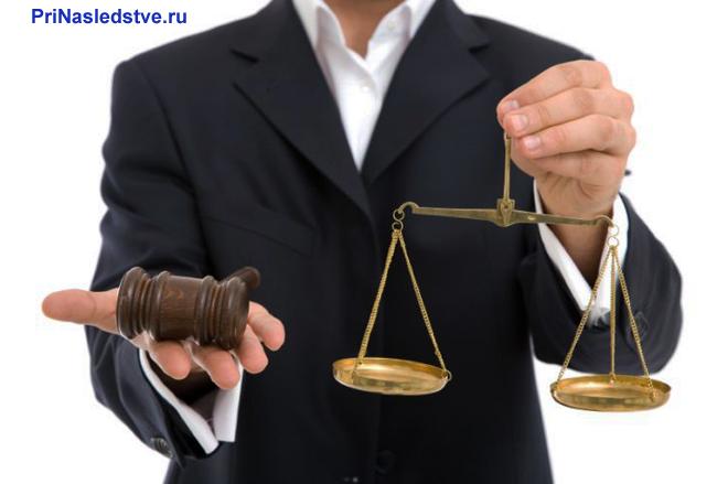 Юрист держит в руках молоточек и весы Фемиды