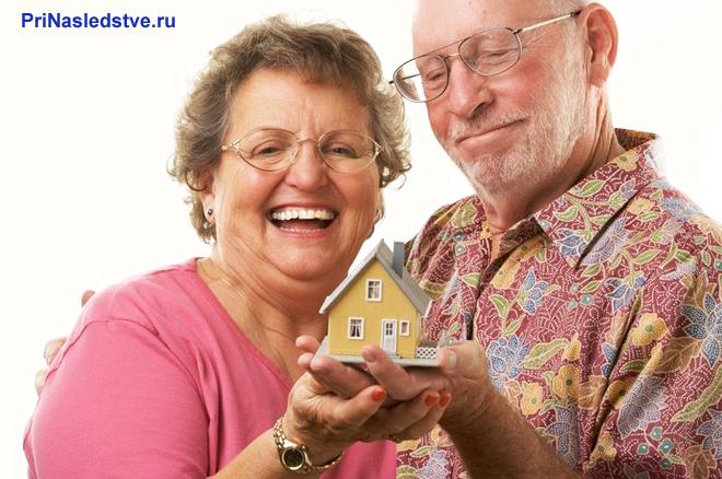 Пожилая пара держит в руках желтый домик