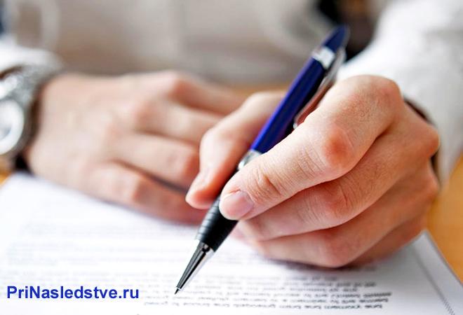 Мужчина пишет на листке бумаги синей ручкой
