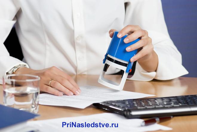 Девушка в белой рубашке сидит за столом и ставит печать на документах