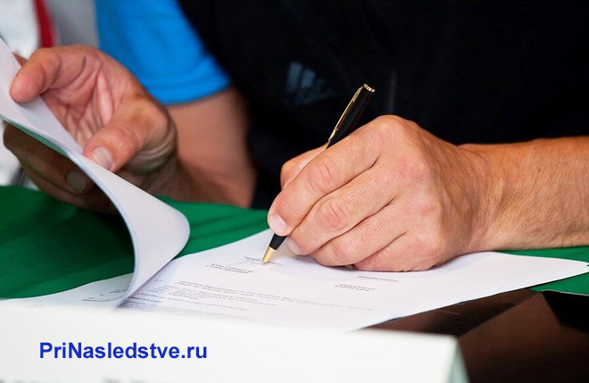 Мужчина ставит свою подпись на заявление