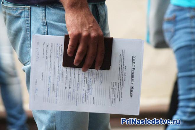 Мужчина стоит в очереди с заявлением и паспортом