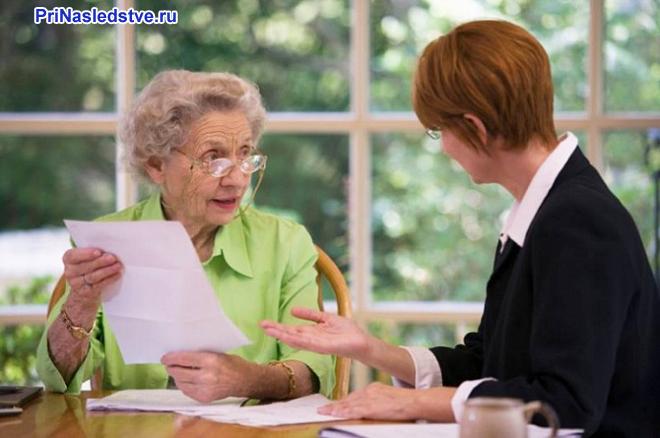 Бабушка и молодая женщина оформляют вместе документацию