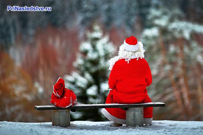 Деде Мороз сидит на скамейке с мешком подарков