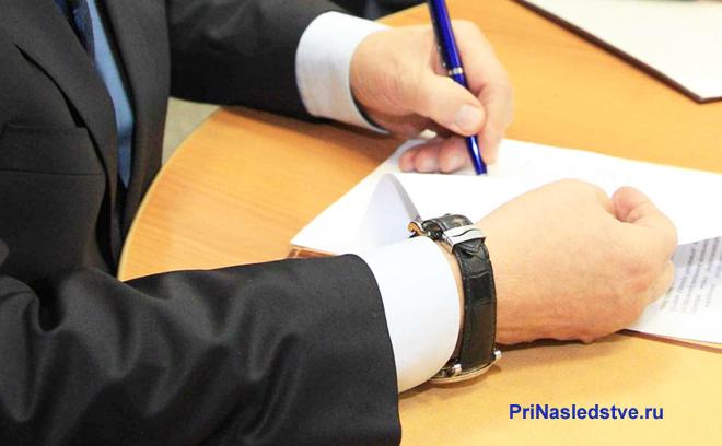 Бизнесмен подписывает документ синей ручкой
