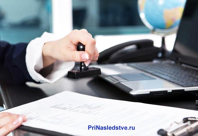 Юрист сидит за своим рабочим местом, ставит печать на документе