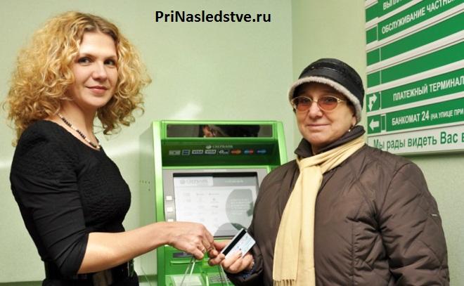 Сотрудница банка и клиентка стоят на фоне банкомата