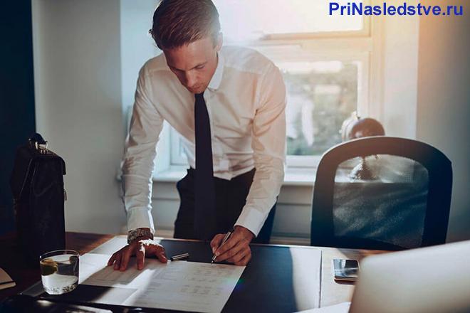 Бизнесмен заполняет бумаги в своем кабинете